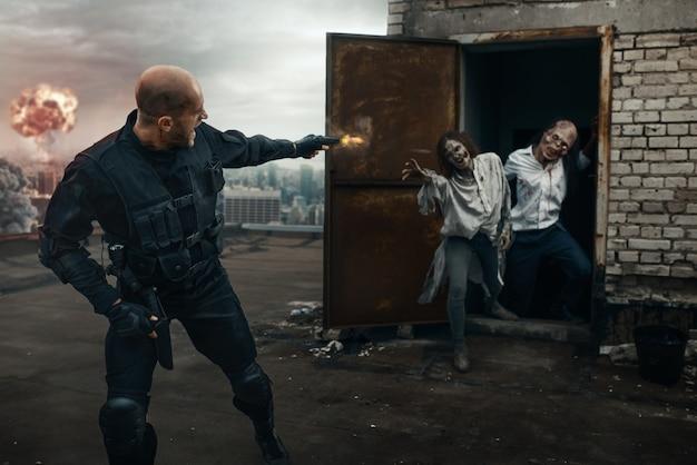 Wojskowy z pistoletem strzela do zombie na dachu budynku