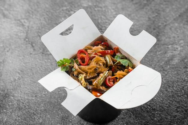 Wok w pudełku makaron ryżowy w czarnym pojemniku na żywność