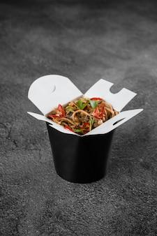 Wok w pudełku pikantny makaron w czarnym pojemniku na żywność