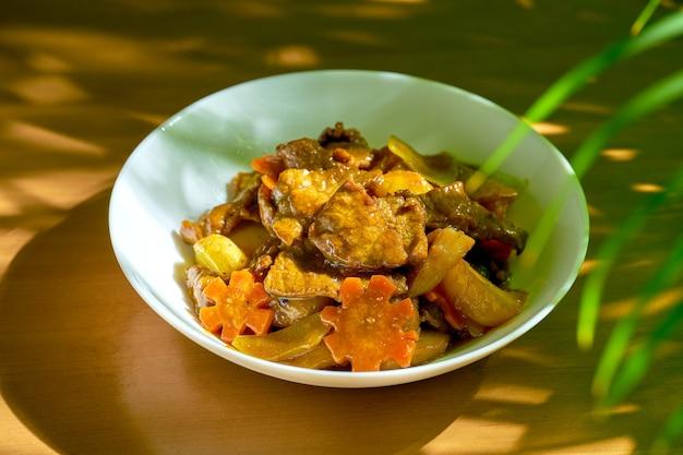 Wok wołowy w sosie słodko-kwaśnym z warzywami i pieprzem syczuańskim w misce. chiński kuzyn