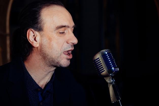 Wokalista mężczyzna z staromodnym mikrofonem