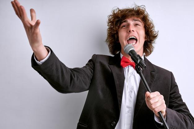 Wokalista na spektaklu śpiewający do mikrofonu, wyrazisty artysta bardzo stara się zadowolić widza, gestami