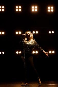 Wokalista śpiewa do mikrofonu. piosenkarka w sylwetce.