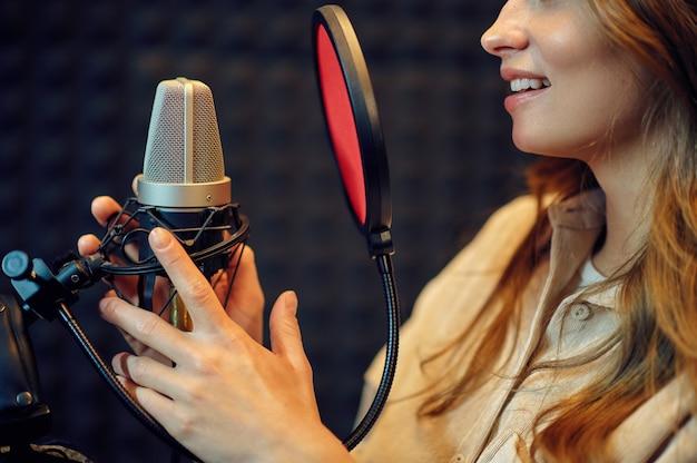 Wokalistka śpiewa piosenkę, studio nagrań