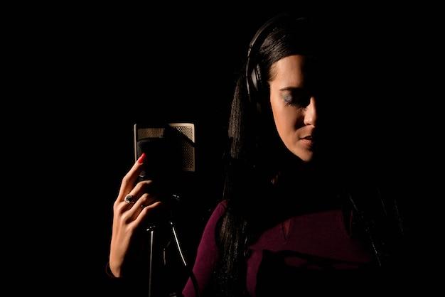 Wokalistka śpiewająca w studiu nagraniowym.