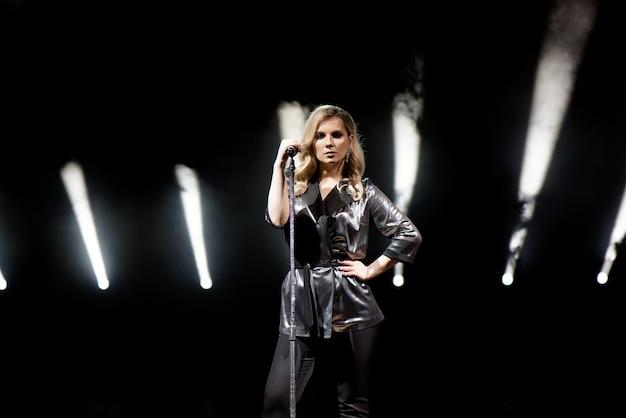 Wokalistka z długimi włosami, trzymająca mikrofon ze stojakiem i śpiewająca.