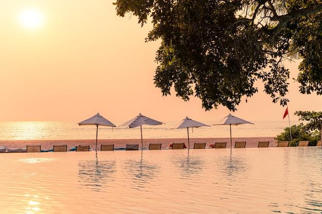 Wokół basenu z widokiem na morze leżaki i parasole