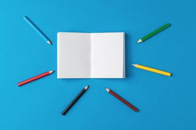 Wokół otwartego notatnika leżą kolorowe kredki. artykuły papiernicze i szkolne.