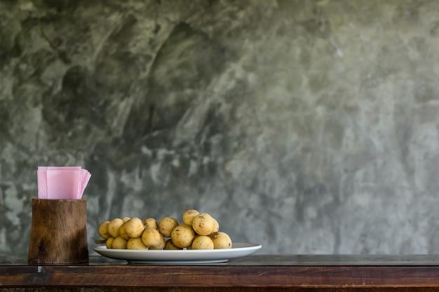 Wollongong w talerzu z tkankami tapetuje na drewnianym stole z ściana z cegieł tłem