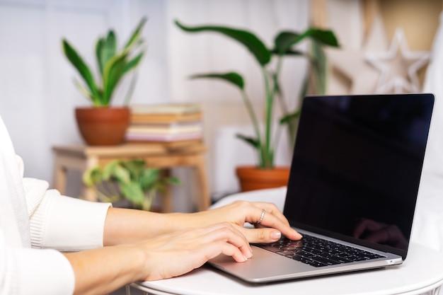 Wolna kobieta pisze na laptopie i robi zakupy online, w pobliżu roślin. szczęśliwa dziewczyna budzi się z domowego biura. kształcenie na odległość, edukacja i praca online.