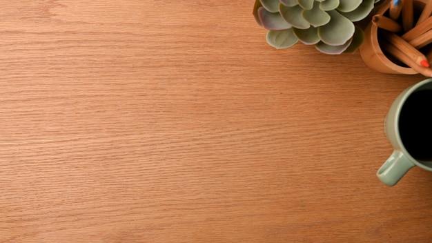 Wolne miejsce na ekspozycję produktu na drewnianym tle z dekoracją papeterii z kubkiem kawy