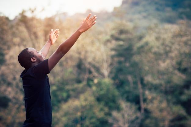Wolność afrykański mężczyzna cieszy się i relaksuje z zielonym tłem w naturalnym.