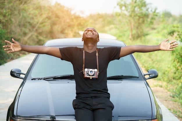 Wolność amerykanin afrykańskiego pochodzenia mężczyzna pozycja z samochodem.
