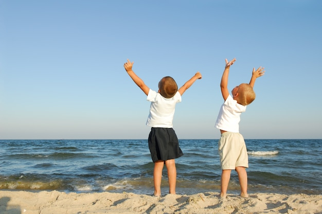 Wolność. dwóch chłopców na plaży z podniesionymi rękami