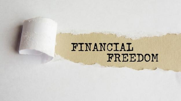 Wolność finansowa. słowa. tekst na szarym papierze na tle rozdarty papier.