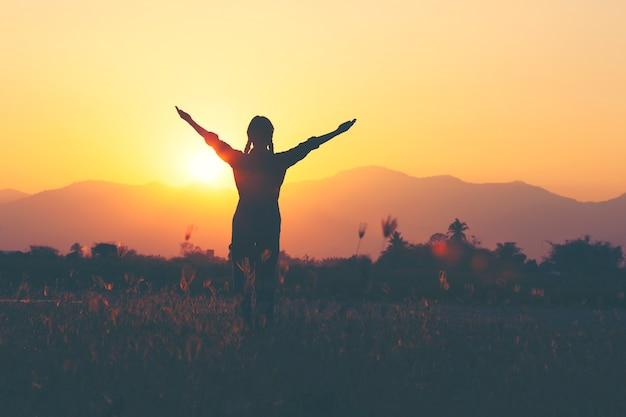 Wolność i sukces - kobieta szczęśliwa przy łąką. darmowe dziewczyny doping z podniesionymi rękami ciesząc się