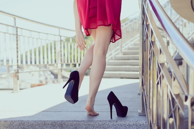 Wolność klasyczna klasyczna sukienka rano wschód słońca po masażu w klubie nocnym nosić koncepcję wyczerpanej dziewczyny. przeczytaj z tyłu widok z bliska zdjęcie pośladków tyłek dłoni zdejmując niewygodne czarne buty