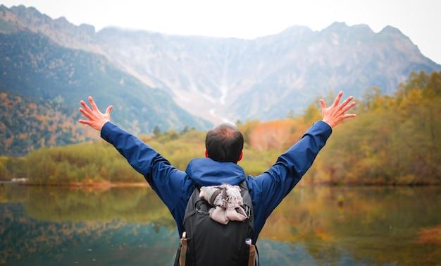 Wolność mężczyzna z rękami up na jeziornej stronie przeciw naturalnym jesień lasem i górom