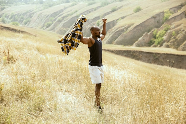Wolność. młody afroamerykański podróżnik mężczyzna stojący pewnie na zielonych łąkach w słoneczny letni dzień. wygląda poważnie, podniósł ręce do góry. lato, wakacje, wakacje, odpoczynek.