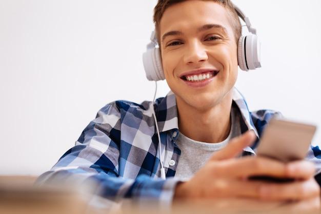 Wolny czas. przystojny, zachwycony powietrznowłosy chłopak, uśmiechając się i nosząc słuchawki, słuchając muzyki i trzymając swój nowoczesny telefon