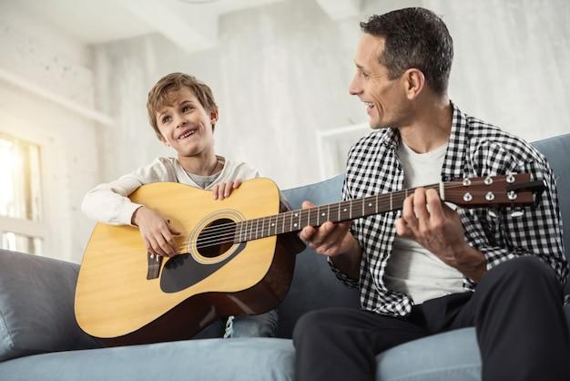 Wolny czas. przystojny, zadowolony mały jasnowłosy chłopiec uśmiecha się i trzyma gitarę, a ojciec uczy go gry na gitarze