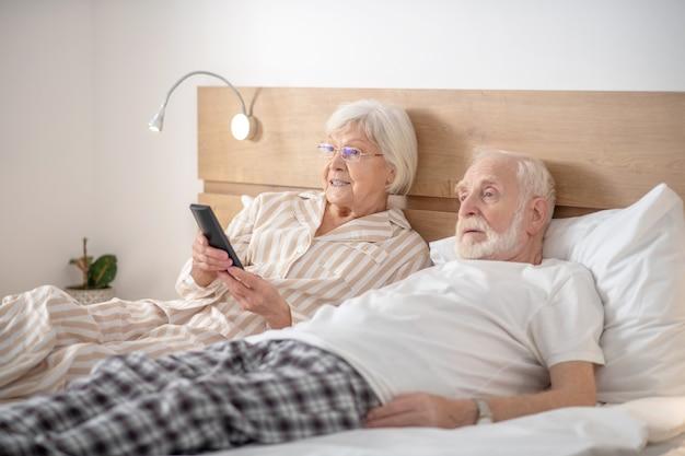 Wolny czas. siwa kobieta i jej mąż odpoczywają w domu