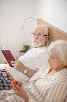 Wolny czas. starsze małżeństwo, leżąc w łóżku, czytając i czując się dobrze