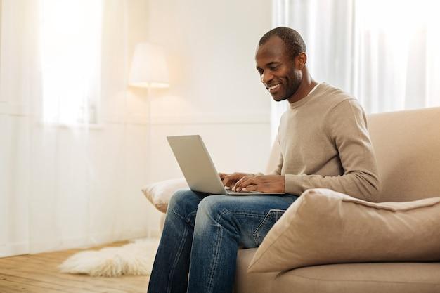 Wolny strzelec. radosny uśmiechnięty afroamerykański mężczyzna piszący na komputerze i patrząc na ekran, siedząc na kanapie i lampie i dywanie w tle