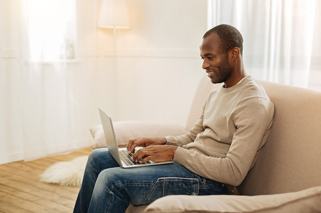 Wolny strzelec. szczęśliwy uśmiechnięty mężczyzna afro-amerykański, wpisując na komputerze i patrząc na ekran, siedząc na kanapie