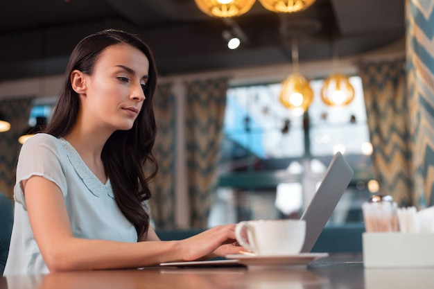 Wolny świat. rozważna młoda kobieta-freelancer wpatrująca się w ekran, pozując na rozmytym tle i pisząc