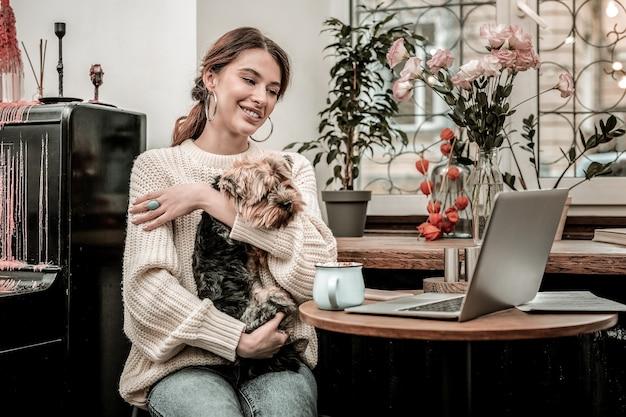 Wolny zawód. kobieta pracująca w kawiarni ze swoim zabawnym psem