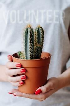 Wolontariat przyjazny środowisku. pielęgnacja i ochrona przyrody. kobieta ze znakiem wolontariusza trzymać kaktusa.
