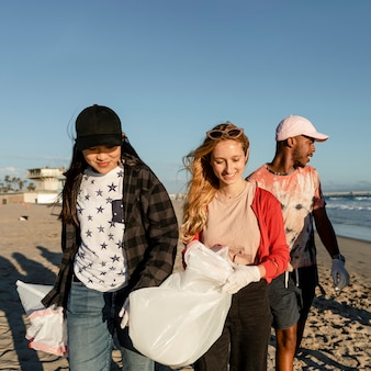 Wolontariat z wywozem śmieci, grupa nastolatków na plaży
