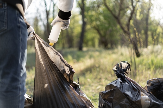 Wolontariusz czyści park z rozrzuconych gruzu, zbierając je do worka. ekologia, koncepcja ochrony środowiska.