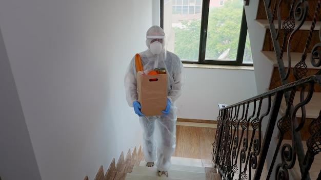 Wolontariusz dostarczający jedzenie w kombinezonie podczas pandemii covid-19.