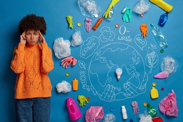 Wolontariusz ekologiczny obok kolażu odpadów środowiskowych