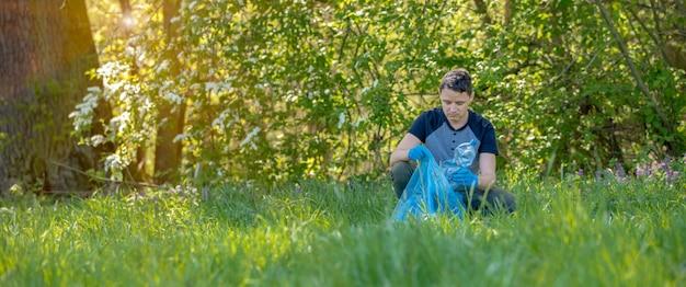 Wolontariusz oczyszcza las ze śmieci, chroni środowisko. kopia przestrzeń
