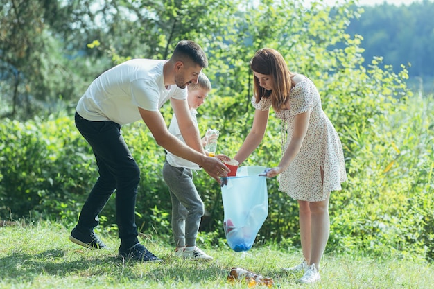Wolontariusz rodzinny sprząta śmieci w przyrodzie. ojciec i matka, rodzice, dzieci, synowie, rodzinni wolontariusze w słoneczny dzień sprzątający butelki na śmieci w lesie, składane w plastikowej torbie