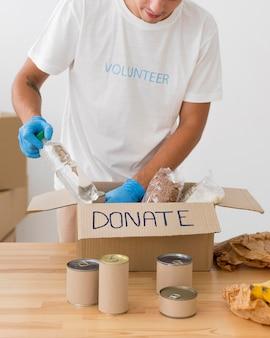 Wolontariusz umieszcza prezenty w pudełkach na datki