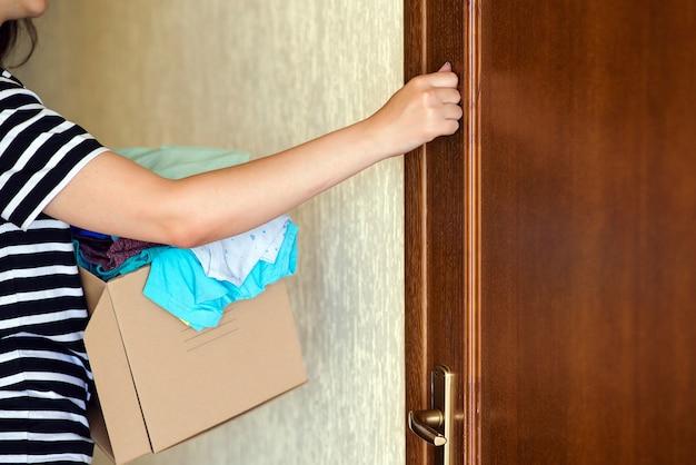 Wolontariusz z pudełkiem na datki puka do drzwi. kobieta trzyma pudełko darowizny.
