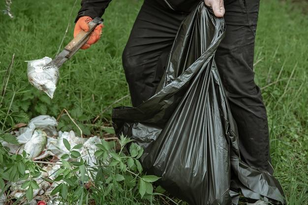 Wolontariusz z workami na śmieci na wycieczkę do natury, sprzątanie środowiska