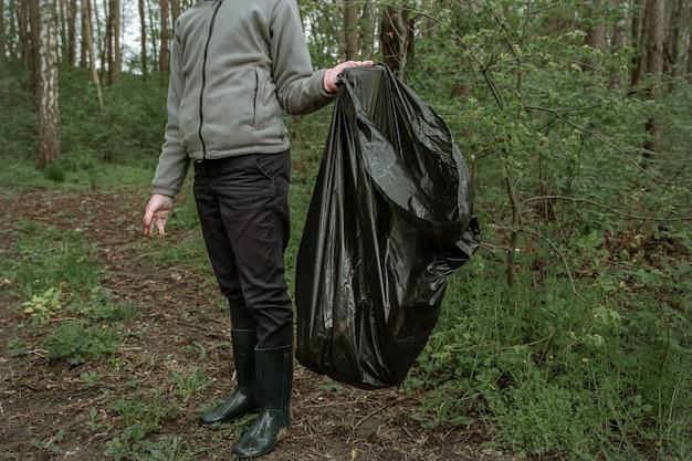 Wolontariusz z workiem na śmieci na wycieczkę do natury, sprzątanie środowiska.