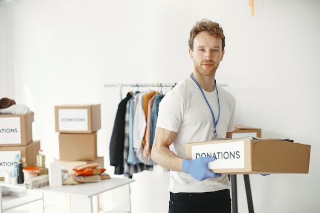 Wolontariusz zbiera rzeczy z darowizn. facet pakuje pudełka z rzeczami. człowiek porównuje wyposażenie.