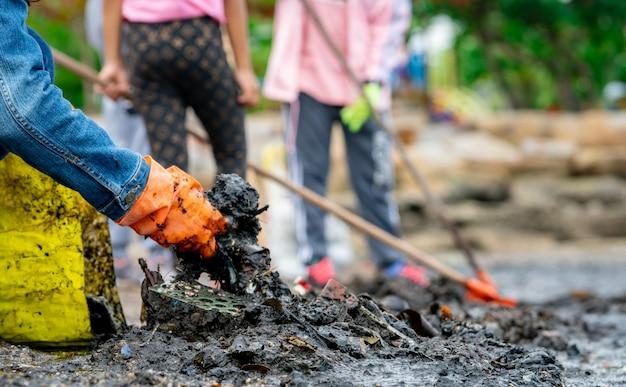 Wolontariusze dorośli i dzieci zbierają śmieci na plaży. zanieczyszczenia środowiska plaży. sprzątanie śmieci na plaży. ludzie noszą pomarańczowe rękawiczki zbierając śmieci do żółtej torby.