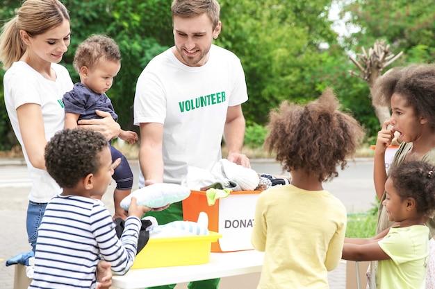 Wolontariusze dzielący się ubraniami i zabawkami z biednymi afrykańskimi dziećmi na świeżym powietrzu