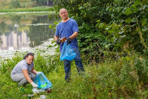 Wolontariusze, kobieta i mężczyzna, sprzątają śmieci na wysypisku w parku. zdjęcie poziome