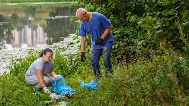 Wolontariusze, kobieta i mężczyzna, sprzątają śmieci na wysypisku w parku.