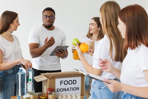 Wolontariusze przygotowują pudełka z darowiznami żywności na tablecie