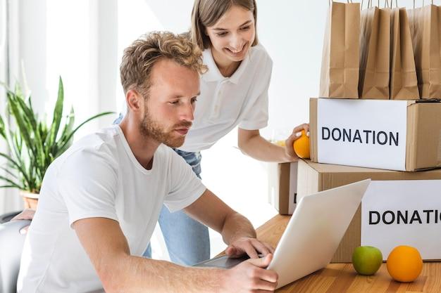 Wolontariusze smiley korzystający z laptopa