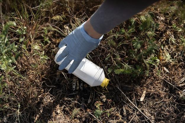 Wolontariusze sprzątają śmieci w parku. ręka nosząca gumowe rękawiczki podnosi plastikową butelkę z trawy.